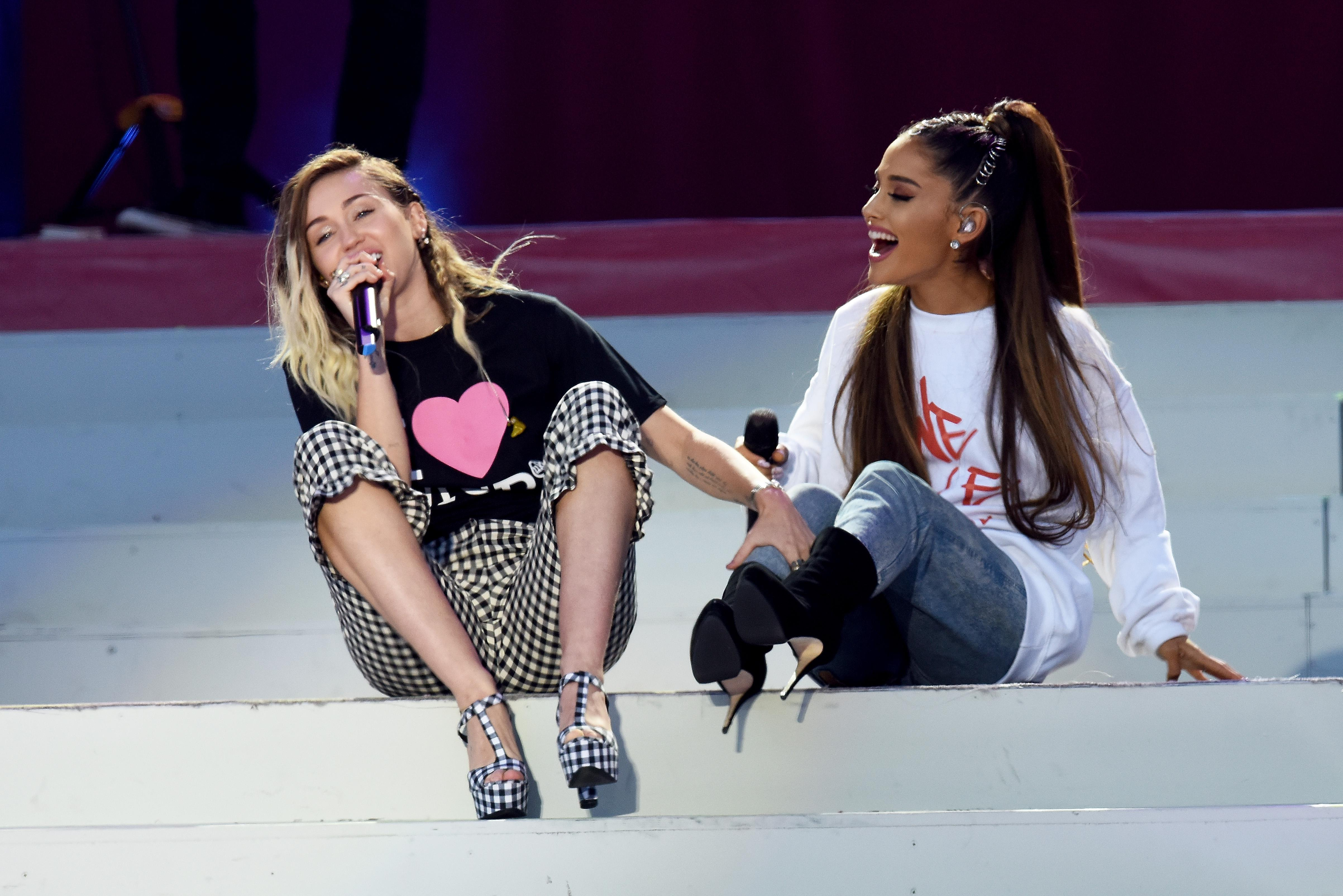 Miley Cyrus and Ariana Grande smile and sit on the white stairs while performing onstage together