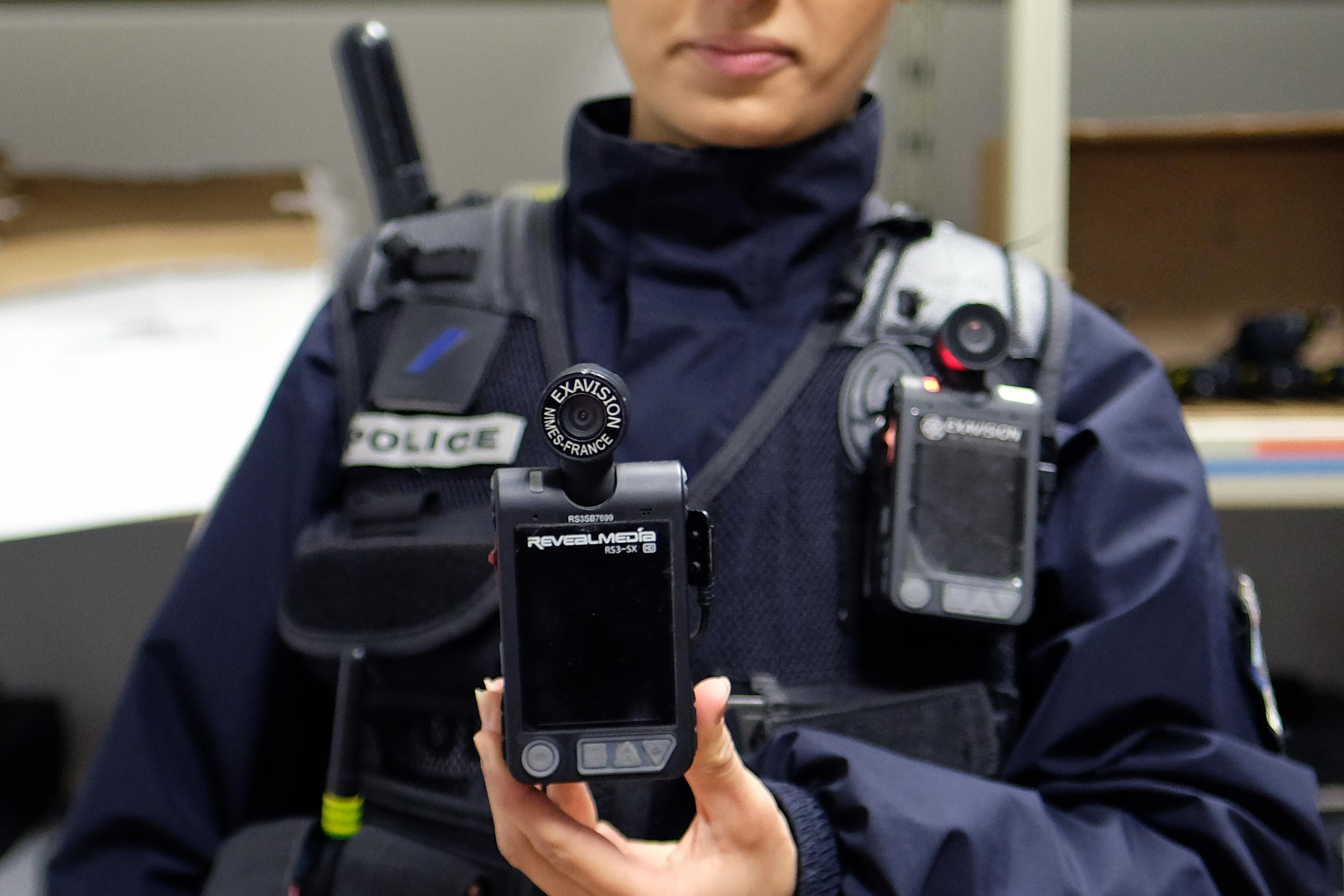 A person in police gear holds up a body camera.