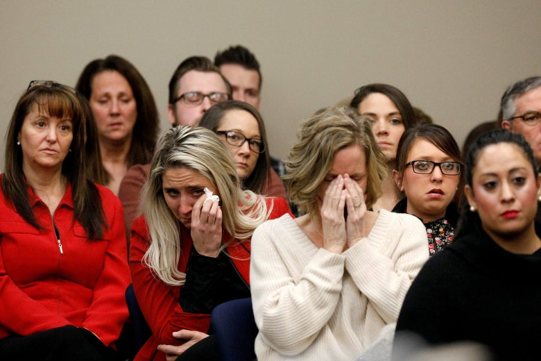 People seated in rows in court. Two women are crying.