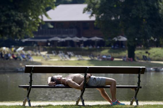 A man sleeps on a bench in a park during a heat wave in Brussels.