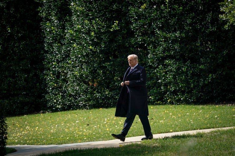 Trump, wearing a suit and a dark coat, walks by himself across a sidewalk against a backdrop of foliage.