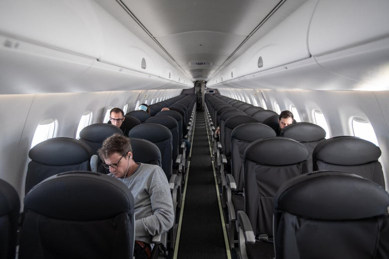 A handful of people seated in a nearly empty airplane cabin.