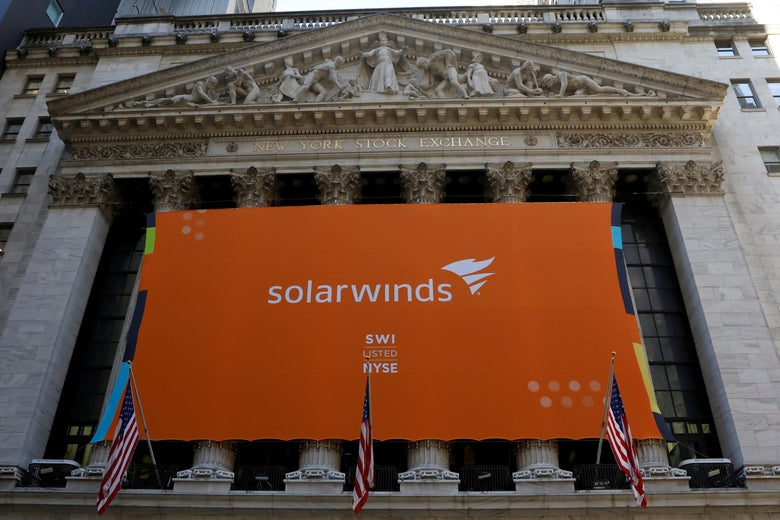 A large orange SolarWinds banner hanging on the front of the New York Stock Exchange building.