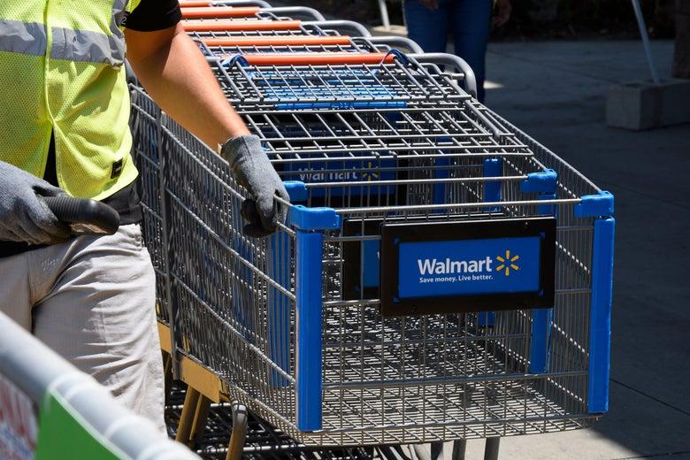 An employee gathers shopping carts