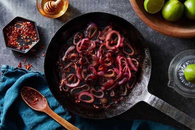Purple onion tendrils in a saucepan.