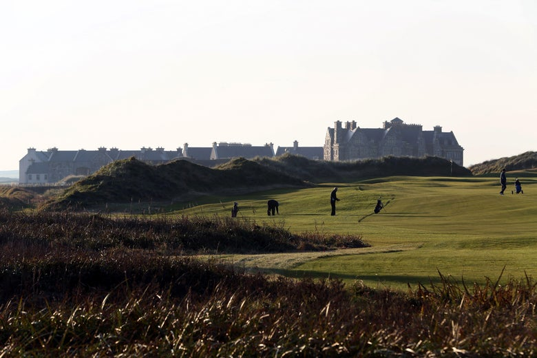 Golfers play on the fairway toward the clubhouse at Trump International Golf Course in Ireland.