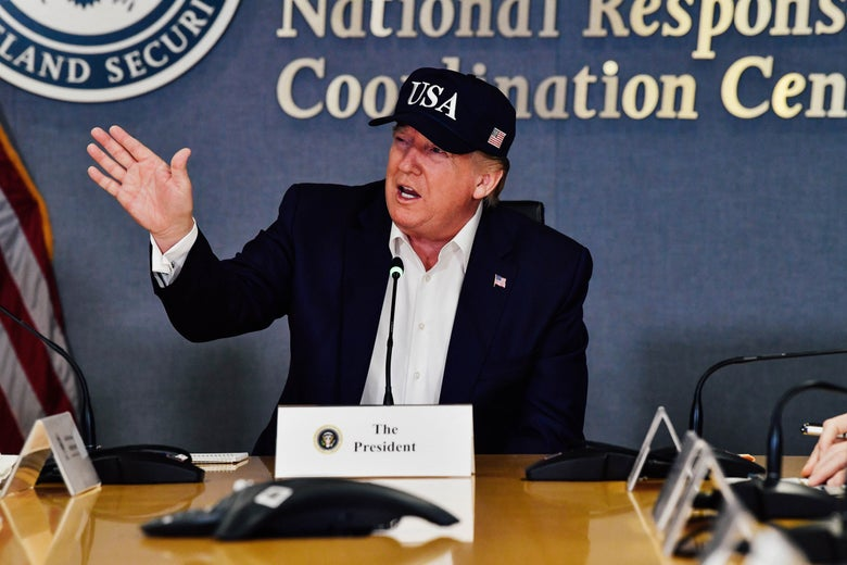 Donald Trump gestures while sitting at a table. He's wearing a USA hat.