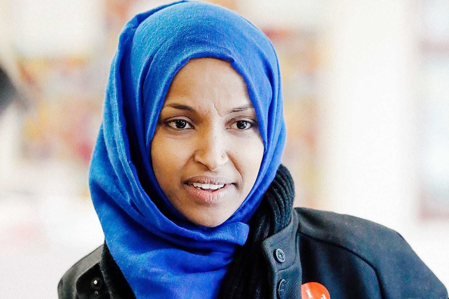Ilhan Omar affixes a political button to her coat on Election Day in Minnesota.