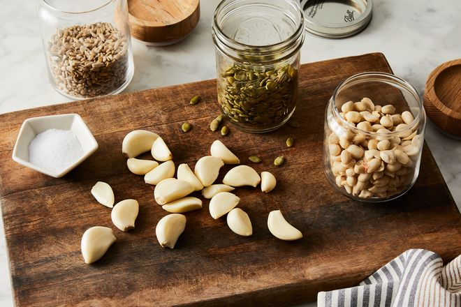 Peeled garlic cloves and several glass gars of seeds sitting on a wooden cutting board.