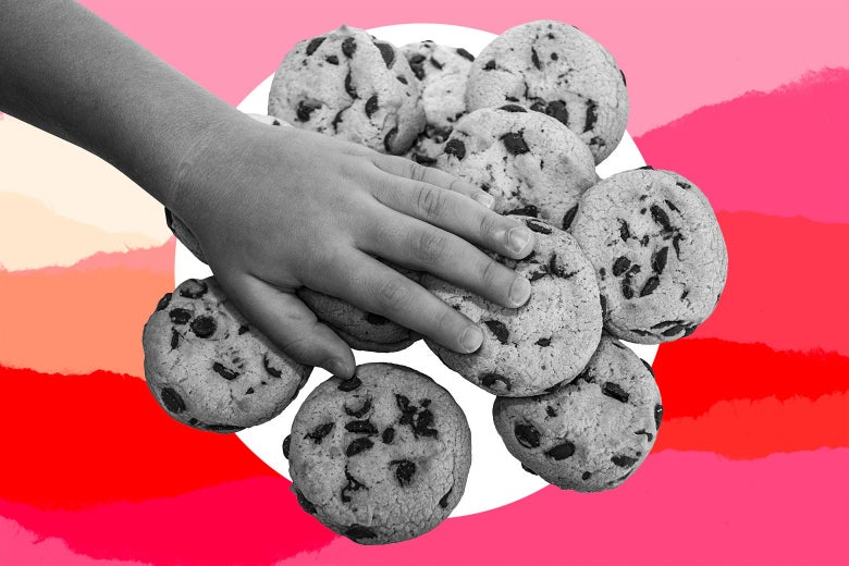 Child's hand on a pile of chocolate chip cookies.