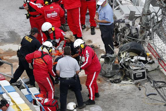 Rescue workers attend to the injured in the stands are an engine and tire (top right) are seen following a last-lap incident.
