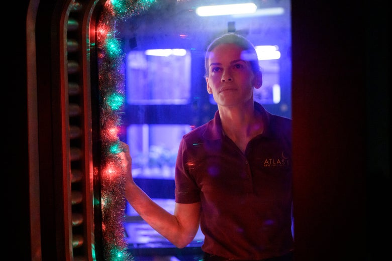 Hillary Swank stands at an airlock door, festooned with Christmas lights.