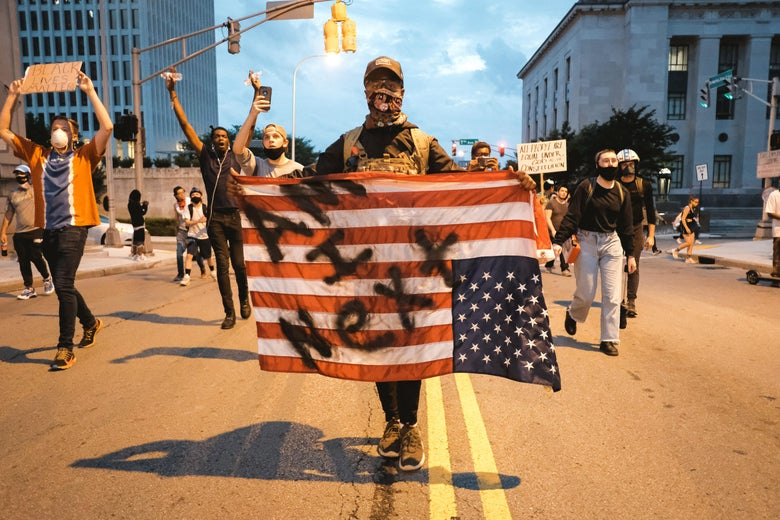 "A man in a bandana holds an upside-down U.S. flag on which can be seen the words ""Am I Next?"" Other protesters walk on the street and hold signs behind him."