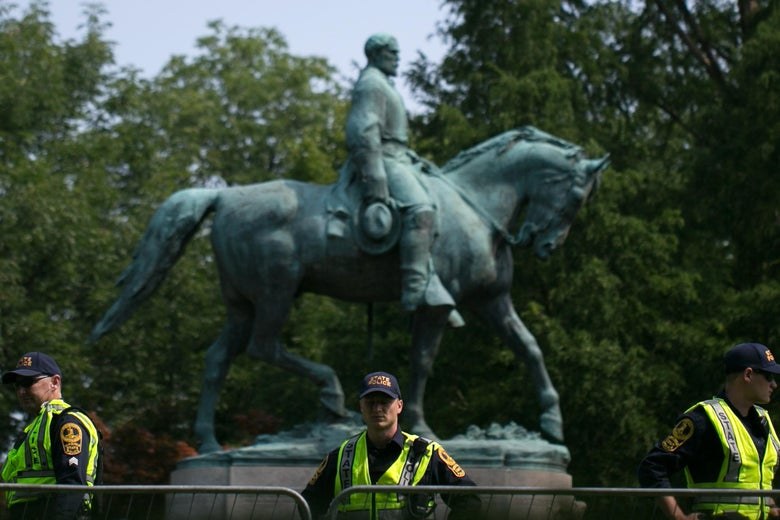 Three officers wearing neon safety vests stand in front of the Lee statue on a sunny day
