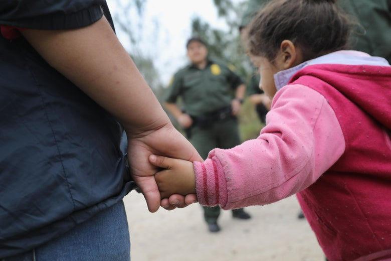 A child holds an adult's hand while a Border Patrol agent stands in the background.