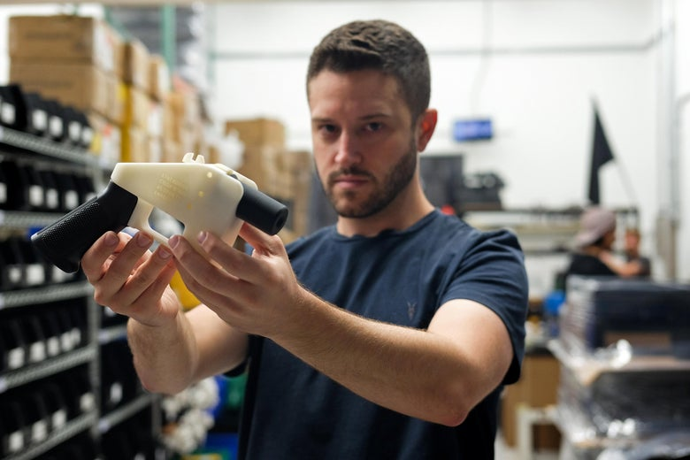 "Cody Wilson, owner of Defense Distributed company, holds a 3D printed gun, called the ""Liberator."""