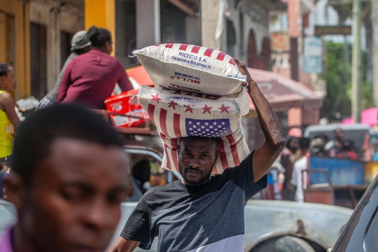 A man walks down the street carrying two bags on rice emblazoned with the American flag.