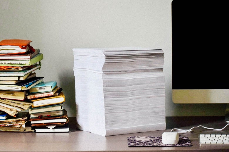 A stack of printed papers on a desk, flanked by a computer and books.