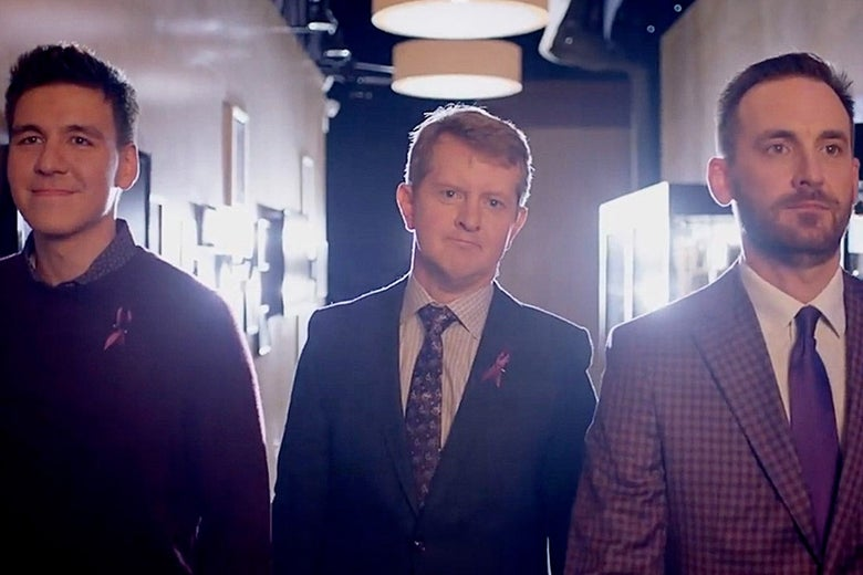 James Holzhauer, Ken Jennings, and Brad Rutter standing side by side in a hallway.