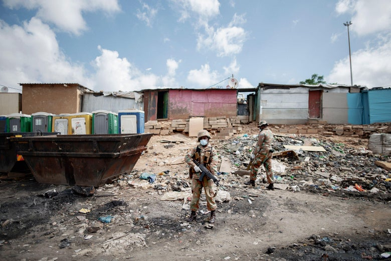 Mask-wearing troops carry guns in front of shanty houses in a South African township.