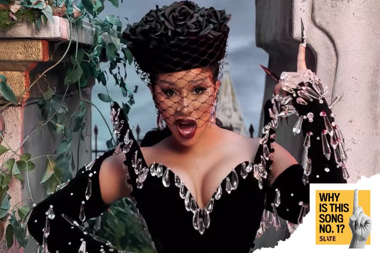 Cardi B in a black dress decorated with chandelier crystals.