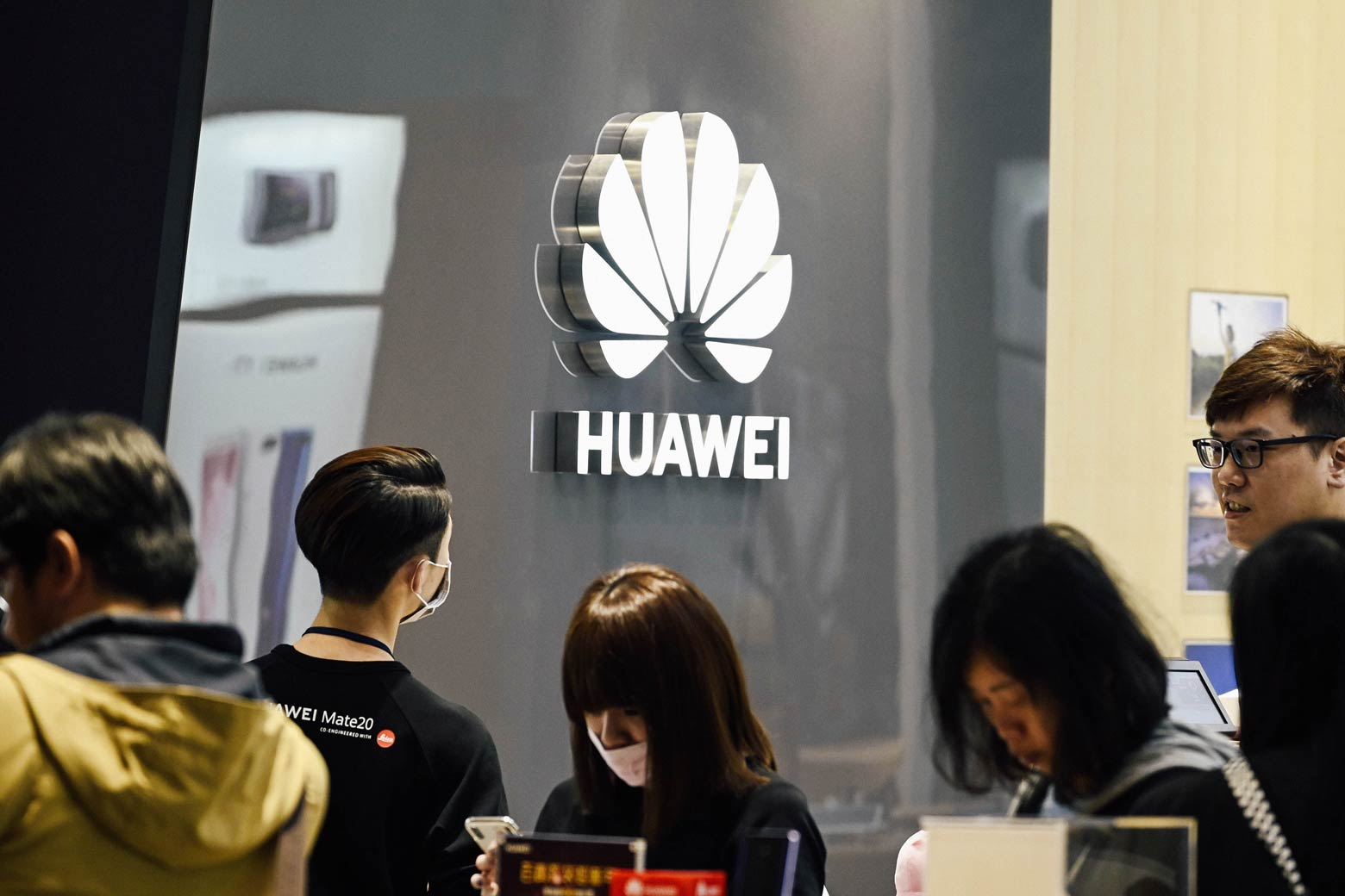 People stand next to a Huawei logo at a mall.