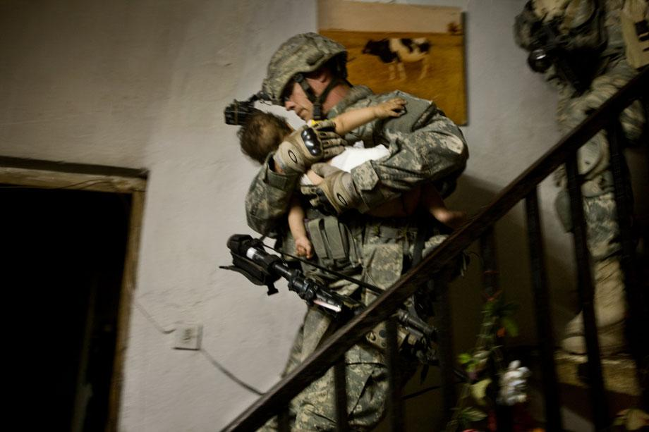 """A soldier of Charlie Company, 1st Battalion, 21st Infantry Regiment """"Gimlets,"""" 2nd Stryker Cavalry Regiment, attached to the 4th Infantry Division's 3rd Brigade Combat Team, and Iraqi soliders of the24th Brigade, 6th Iraqi Army Division, carries a child during a raid in Abu Ghraib, Anbar province, Iraq on April 6, 2008. The raid began before dawn this morning in which they sought out """"high-value"""" al Qaeda targets involved in kidnapping and murder. They searched several houses but did not find the suspects they were looking for."""