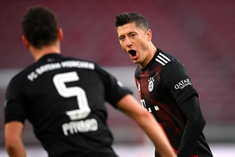 Lewandowki yelling in celebration on the pitch at Pavard as Pavard approaches him