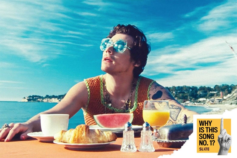 "Still from the ""Watermelon Sugar"" video in which Harry Styles, wearing sunglasses, sits at a table on the beach with a slice of watermelon, a croissant, orange juice, a coffee cup, a butter dish, and salt and pepper shakers in front of him"