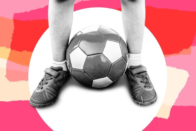 A soccer ball between a boy's feet.