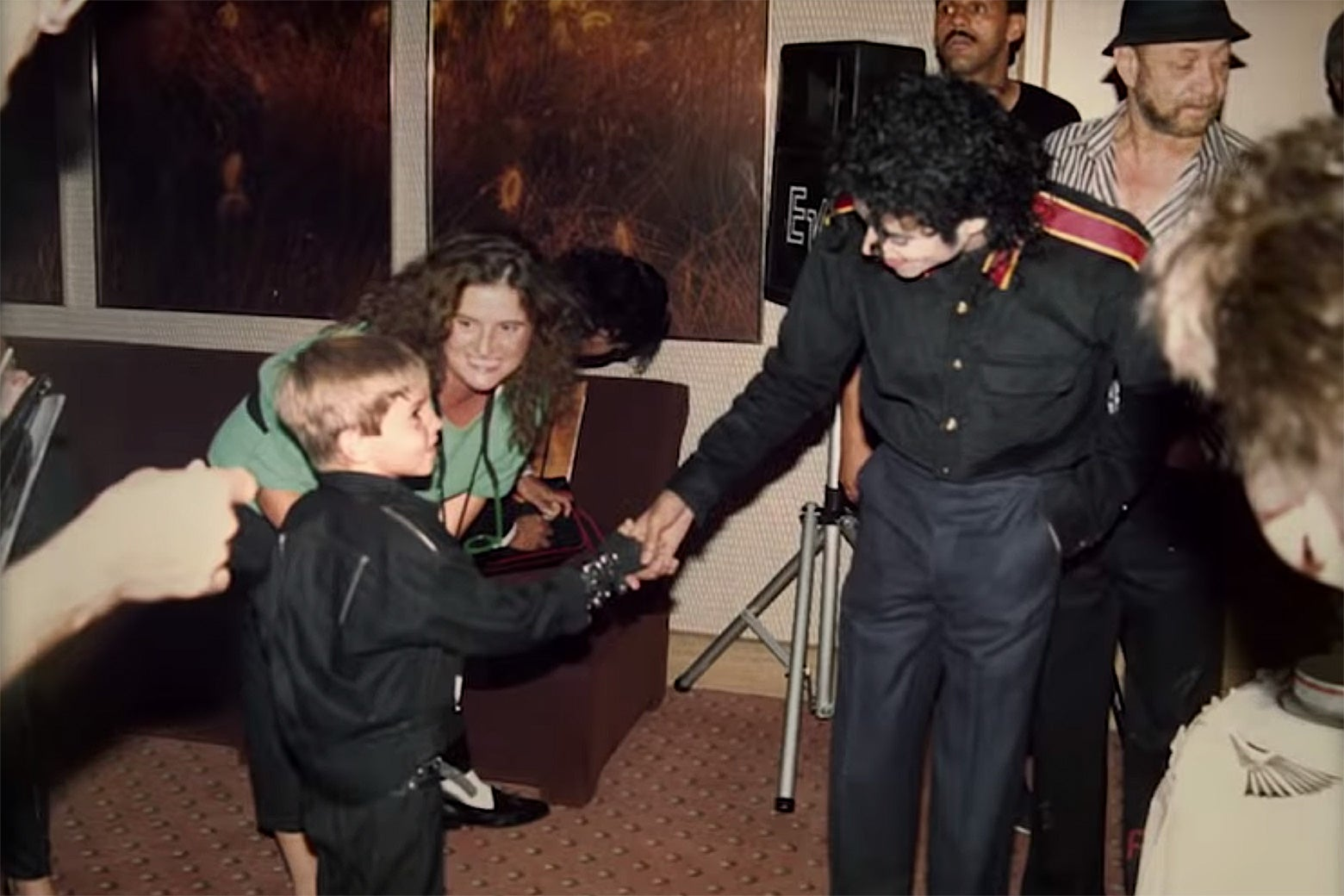 Michael Jackson shaking hands with a young James Safechuck dressed in an outfit inspired by the album Bad.