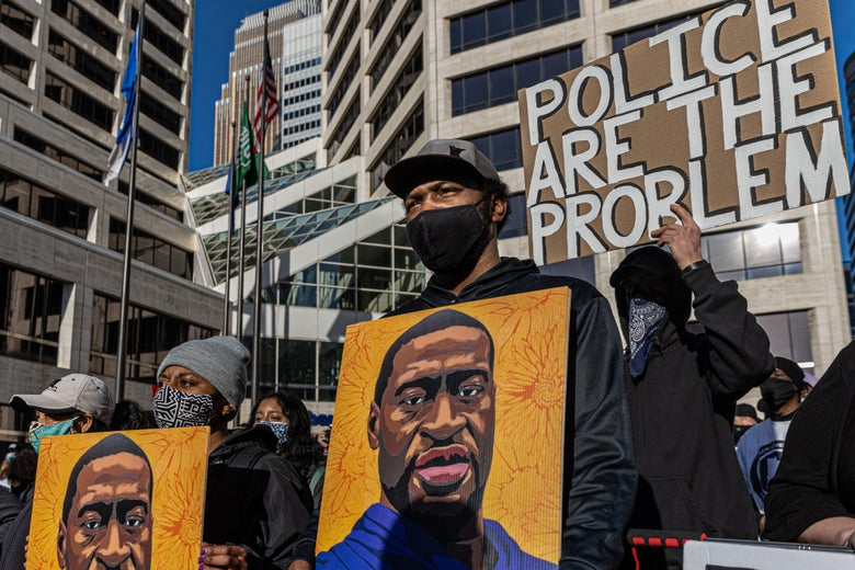"""Protesters in masks hold up paintings of George Floyd and signs that say things like, """"Police are the problem."""""""