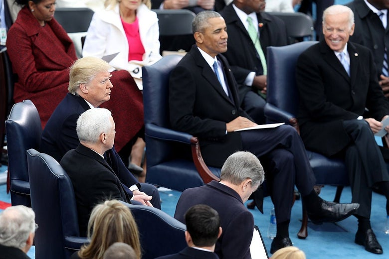 Biden, smiling, looks past Barack Obama toward Donald Trump as they are seated on a dais surrounded by other dignitaries.