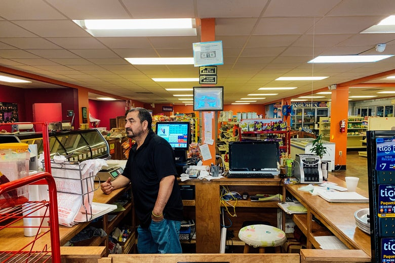 Juan Garcia stands at the register of his deserted grocery store.