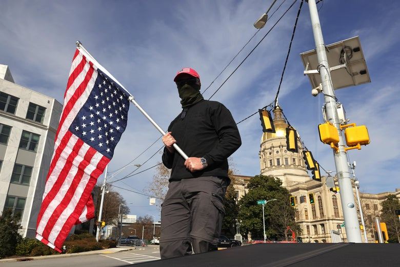 Man wearing black clothing, a black gaiter, and a red MAGA hat holds an upside-down American flag as he stands at an intersection. The Capitol can be seen in the distance behind him.