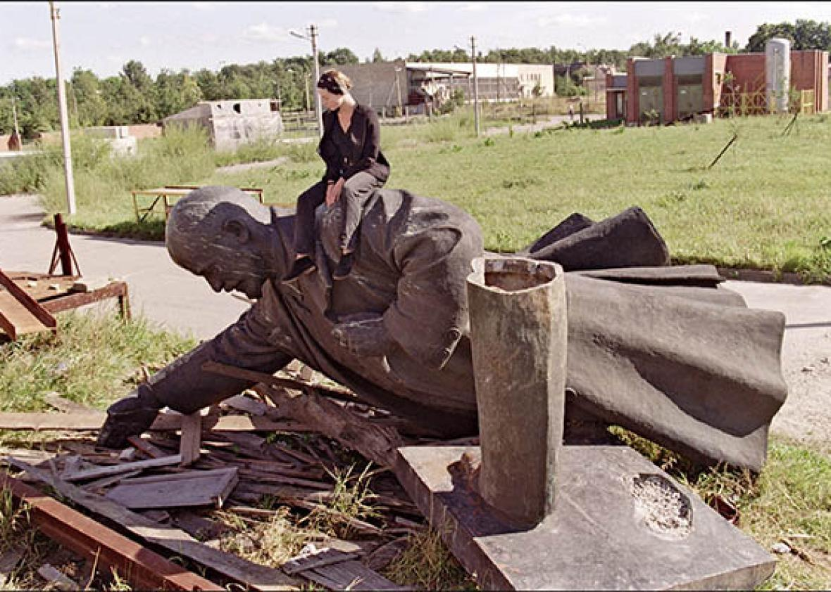 Lithuanian girl sits on the toppled statue of Vladimir Lenin.