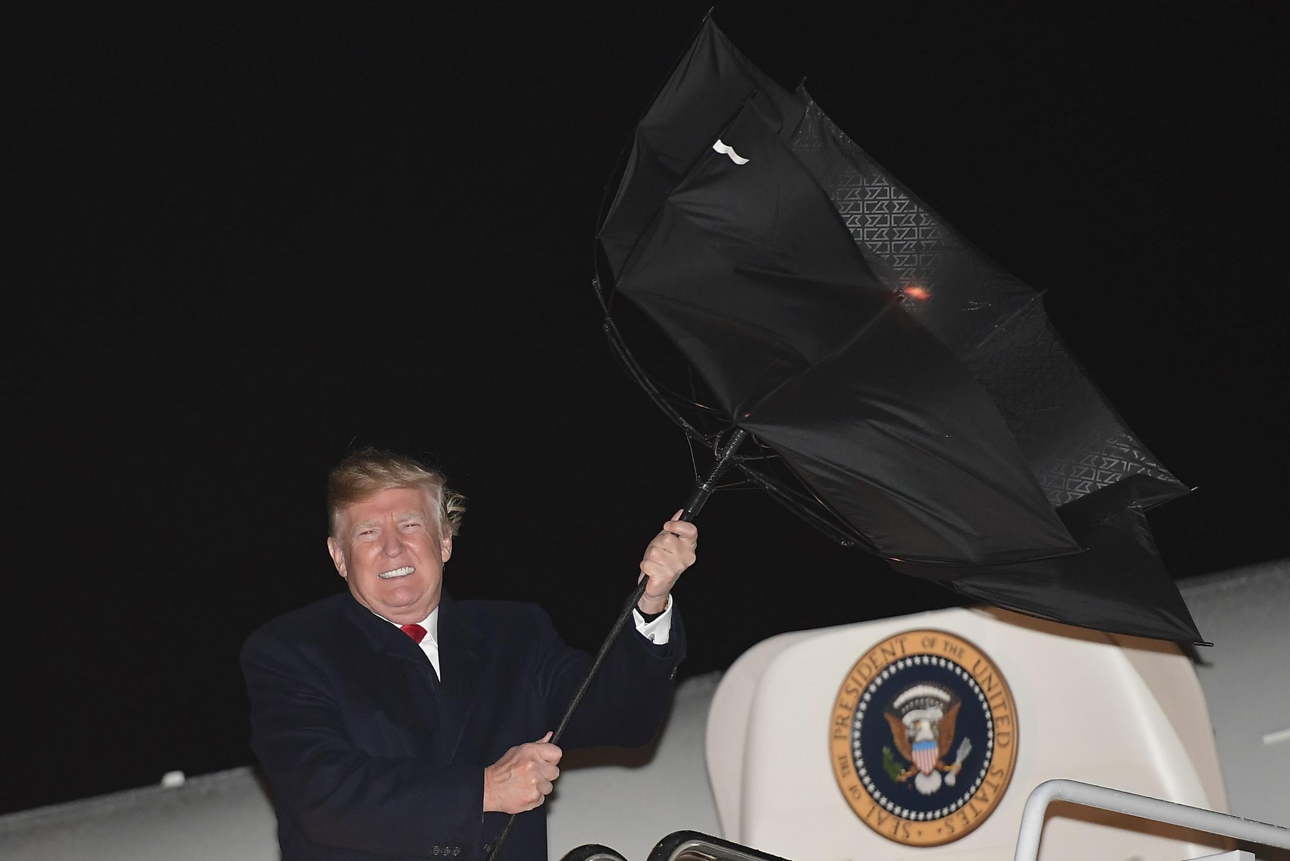 Donald Trump struggling with a broken umbrella.