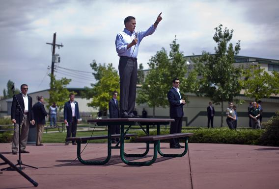 Mitt Romney hops on a picnic table in colorado.