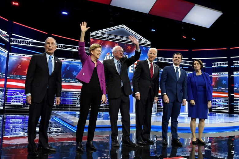 Bloomberg, Warren, Sanders, Biden, Buttigieg, and Klobuchar stand in a line on the debate stage. Warren and Sanders are waving.