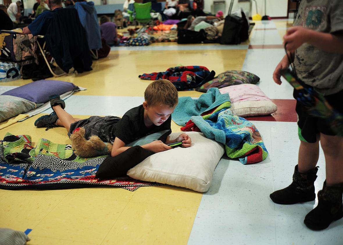 Shawn Miller plays on a cell phone laying on the floor of a makeshift shelter at the Timberlin Creek Elementary School in St. Augustine, Florida, on October 6, 2016, ahead of hurricane Matthew.