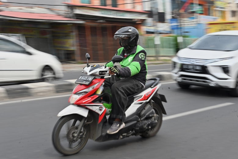 A person on a motorbike drives down a street.