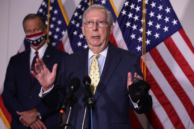 Mitch McConnell speaks into two microphones while standing in front of John Thune and some American flags.