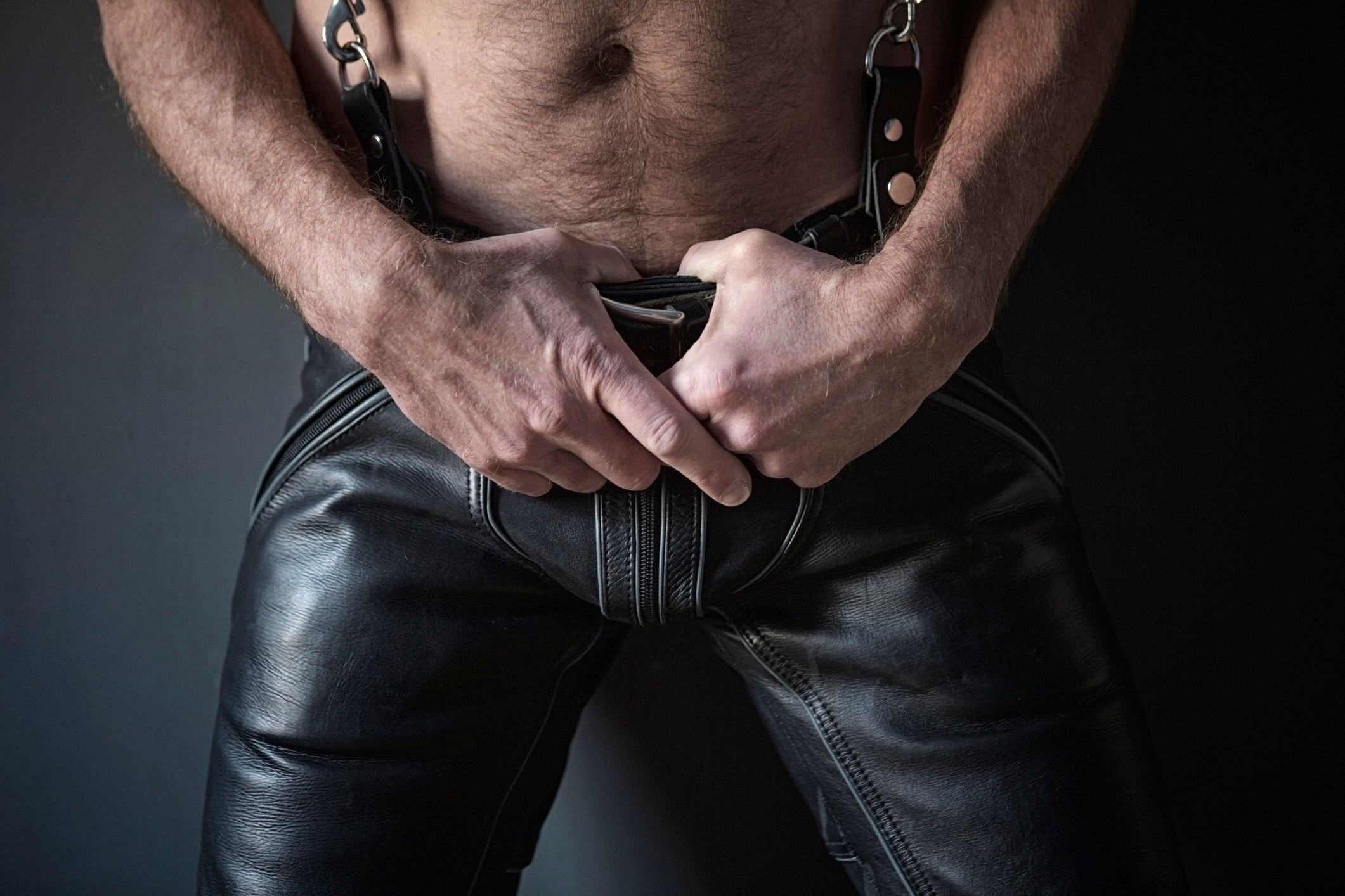 A leather man's lower body, hands on belt.