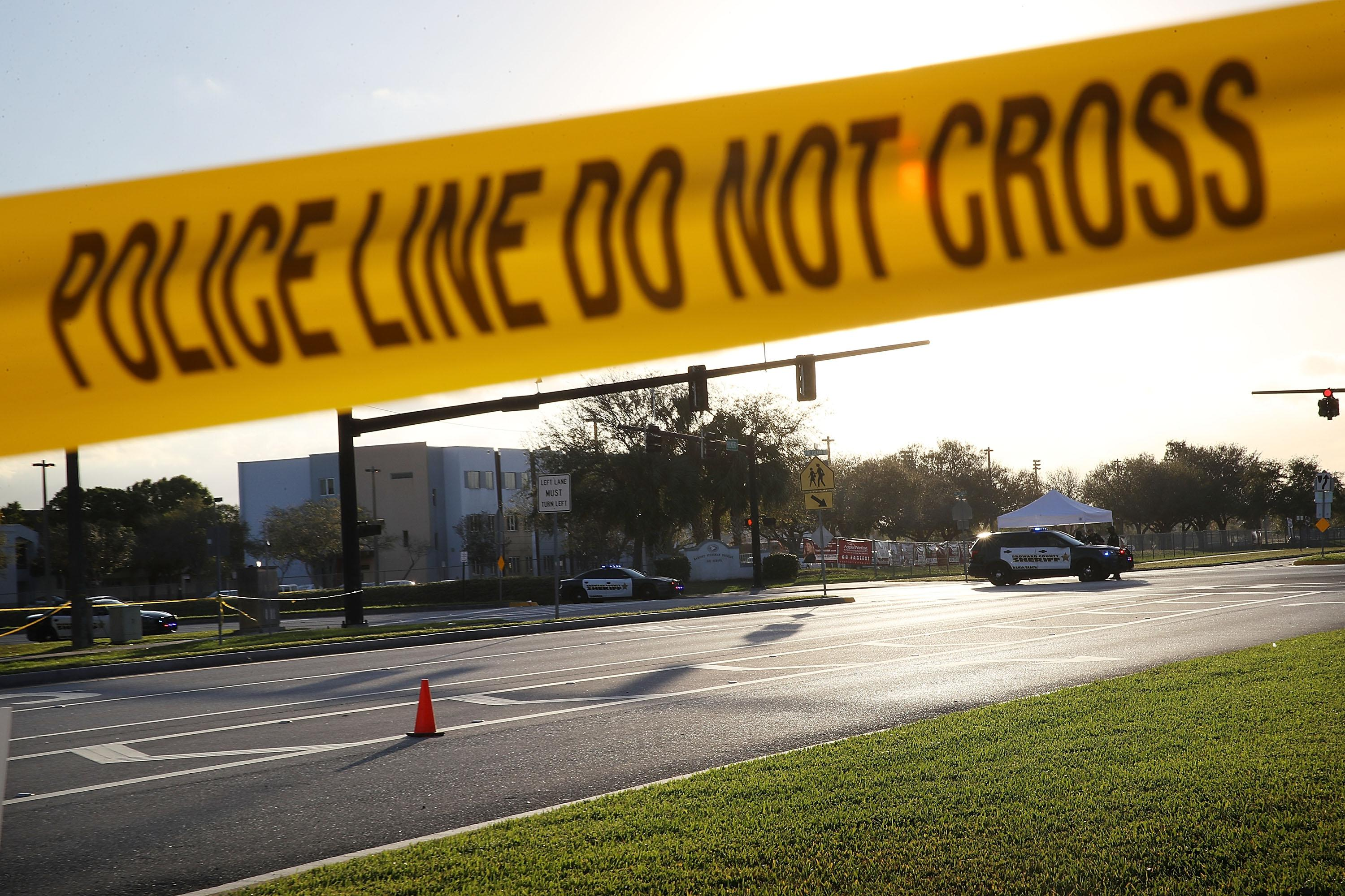 "Police and caution tape reading ""Police Line Do Not Cross"" in front of Marjory Stoneman Douglas High School in Parkland, Florida"