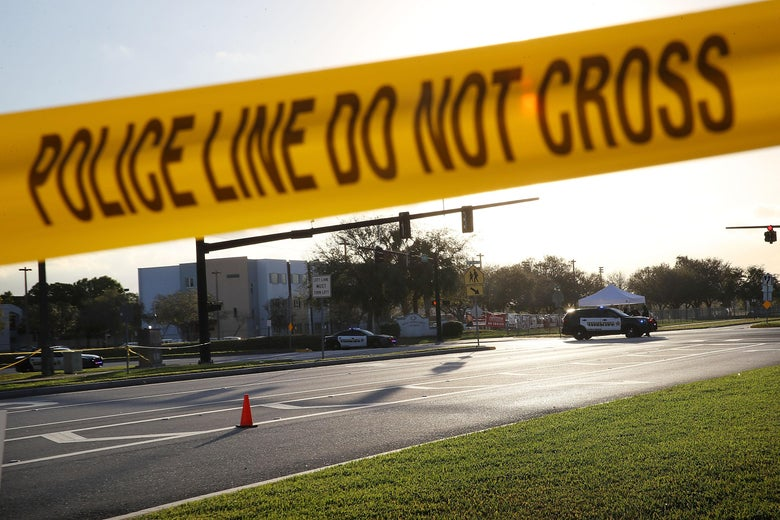 """Police and caution tape reading """"Police Line Do Not Cross"""" in front of Marjory Stoneman Douglas High School in Parkland, Florida"""