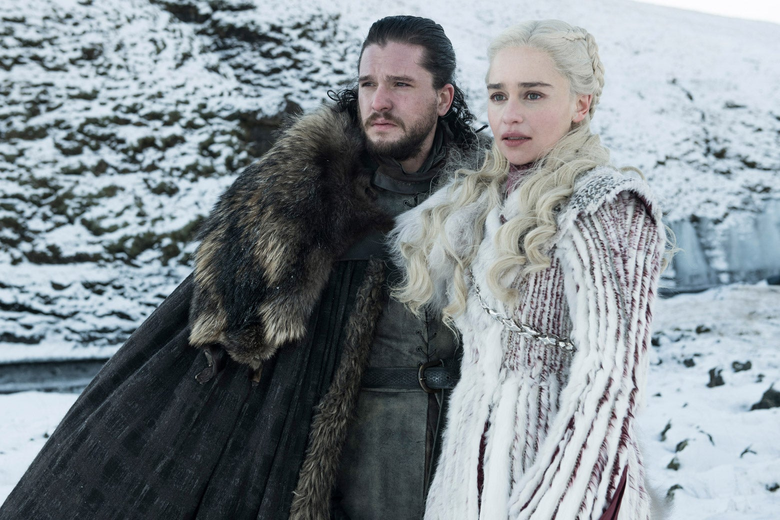 In a still from Game of Thrones, Jon Snow and Daenerys Targaryen stand beside each other in a snowy landscape.