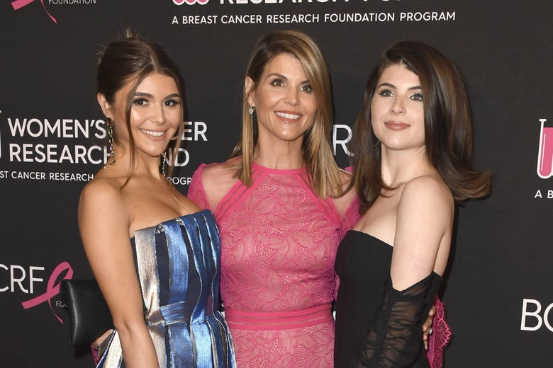Olivia Jade Giannulli, Lori Loughlin, and Isabella Rose Giannulli standing together in formalwear in front of a step-and-repeat for the gala they're attending behind them.