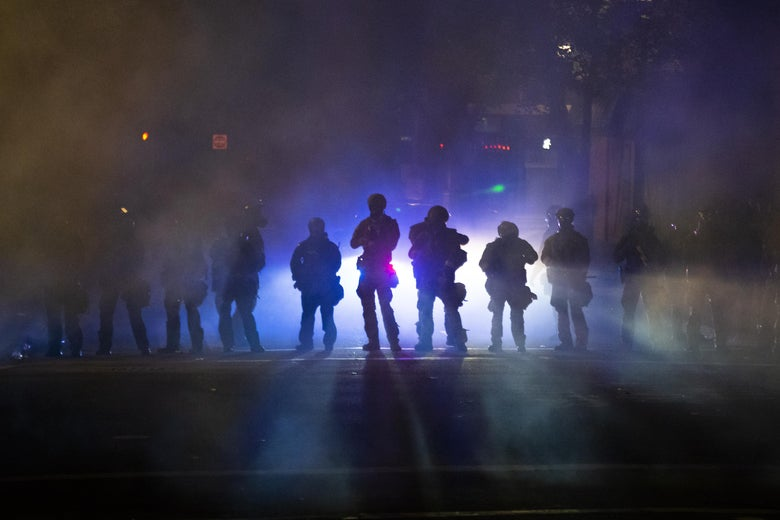 Heavily armed officers seen through smoke and tear gas.