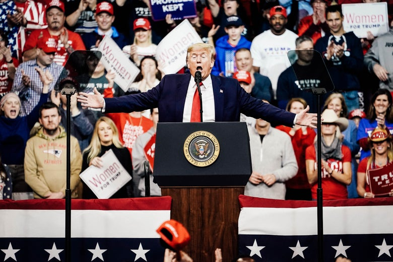 Trump stretches his hands while speaking at a lectern at a rally. A crowd is seen in the stands behind him.