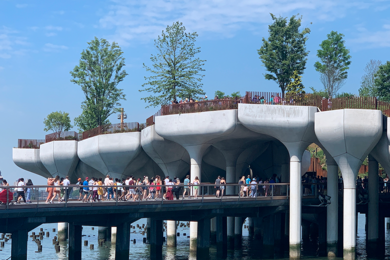 Visitors walk along a gangway to Little Island, which is made up of concrete potlike structures suspended above the Hudson River and grouped together to form a park
